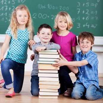 Kinder hinter einem neuen Bücherstapel vom Förderverein