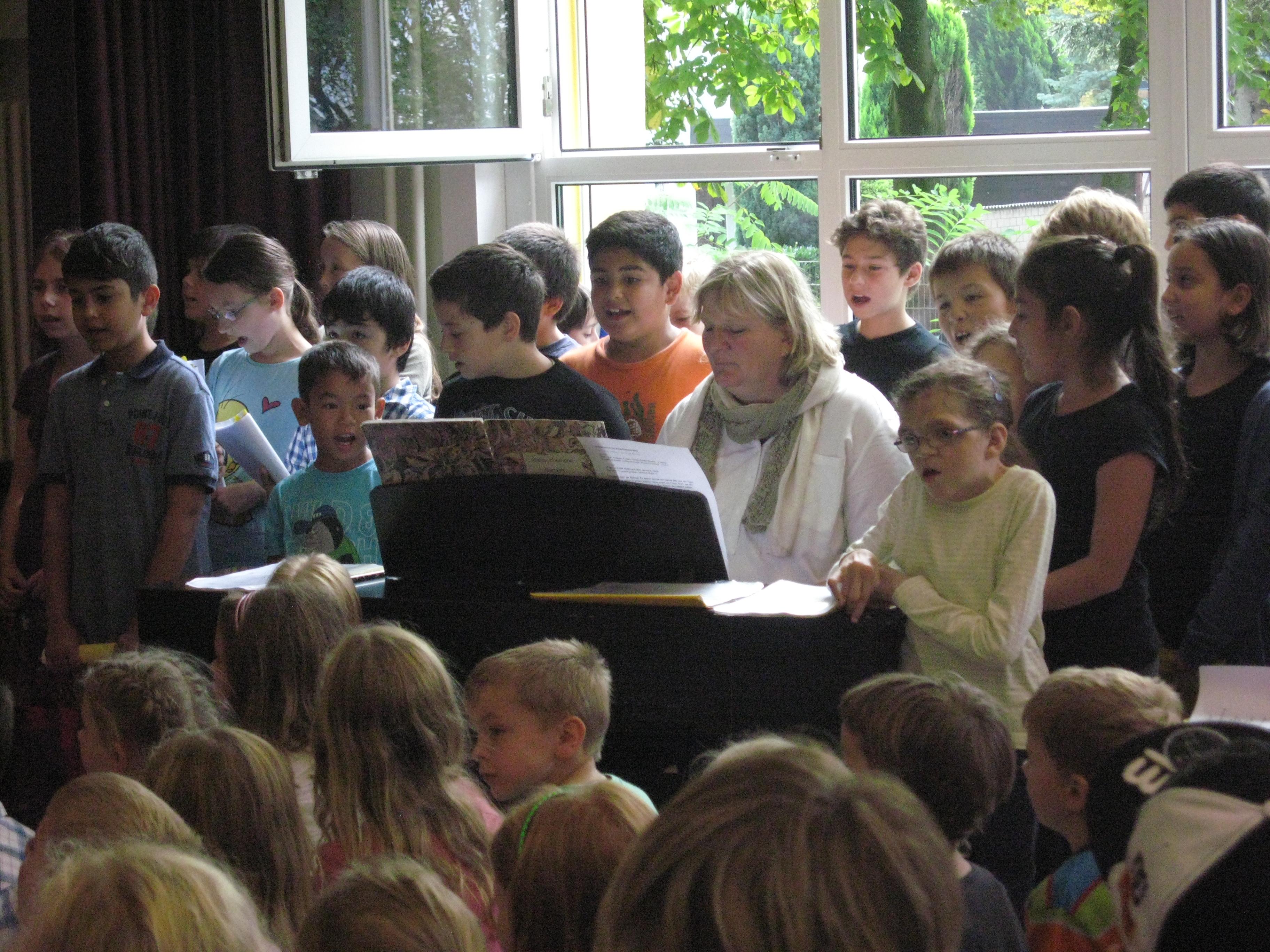 Kinder der Chor-AG stehen um das Klavier und singen